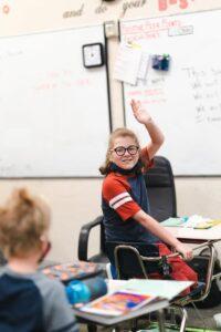 Student sitting at desk hand raised