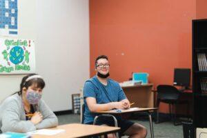Student sitting at desk smiling at camera