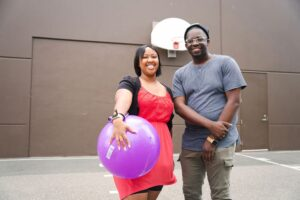 Two Instructors standing side by side smiling at camera, one holding an inflatable ball, basketball hoop in background outside