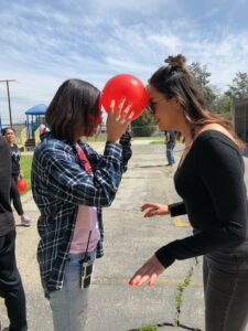 Chino Hills - CVUSD Alternative Education Center - two women outside with balloon between their foreheads