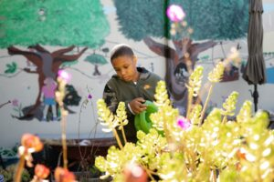 student standing in front of muraled wall at Tara Hills campus watering plants with watering can