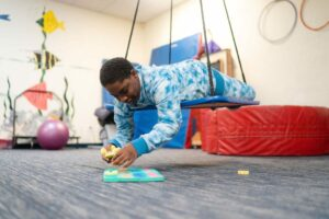 Student laying in swinging platform working with foam alphabet on floor