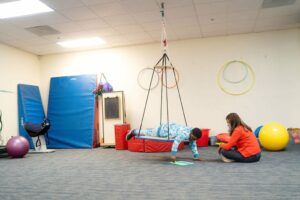 Student laying in swinging platform working with foam alphabet on floor with instructor sitting on floor nearby