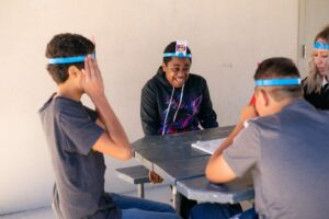 Students sitting around table playing a game outside