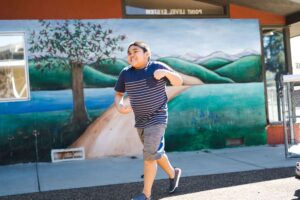 Student running happily across pavement in front of muraled wall at Valley campus