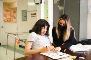 Student working with worksheets with masked teacher helping