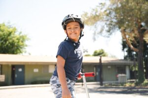 Student on scooter, smiling at camera, wearing helment