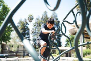 Student climbing up playground equipment