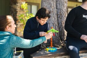 Students playing with toys outside in front of tree