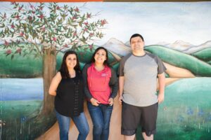 three of the Valley campus staff standing in front of mural